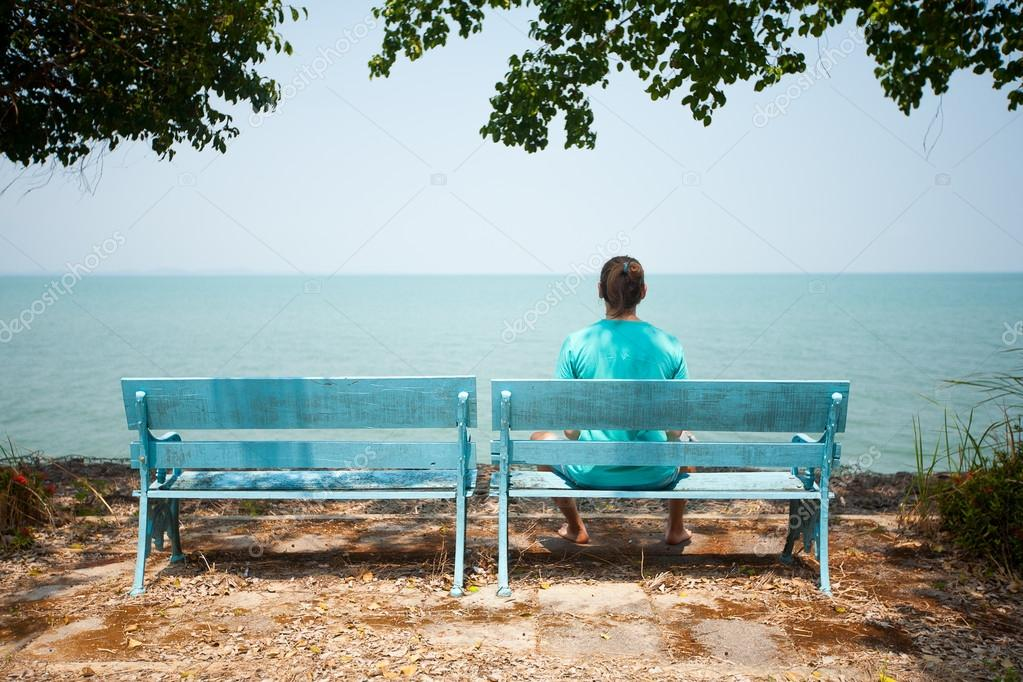 Young man sitting on bench facing the sea