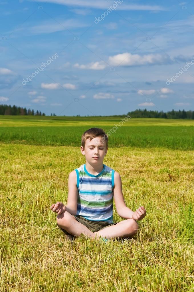 boy meditating on the green field