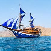 starou dřevěnou lodí s modrými plachtami