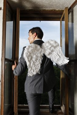 Businessman with angel wings looking through window