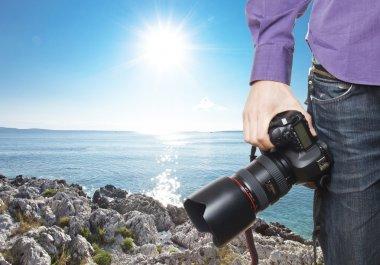 photographer's hand holding professional digital camera on rocky