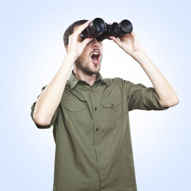 young man looking through binoculars, surprise face expression