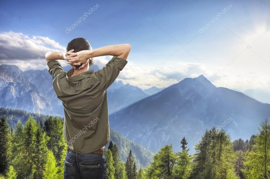 young man on top of the mountain, realxing and enjoying the view