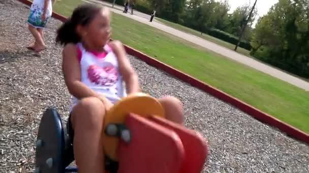 Ein junges Mädchen spielt auf dem Spielplatz.