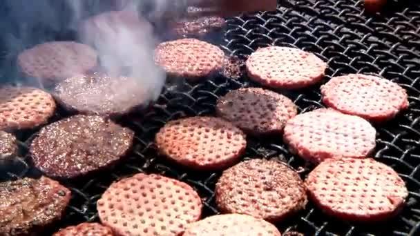 obracející hamburgery na grilu