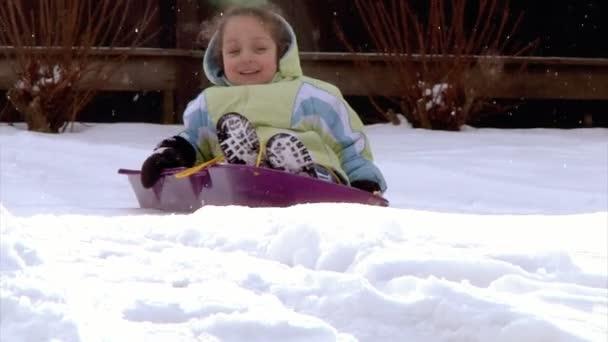 Ein kleines Mädchen fährt Schlitten. Zeitlupe.