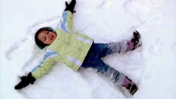 A little girl makes snow angels in the snow.