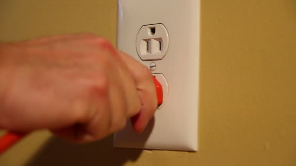Close-up shot of a man plugging and unplugging an orange electrical cord into a U.S. wall outlet.