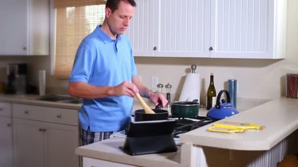 muž vaří při pohledu na jeho dotykový počítač, ipad pro orientaci.