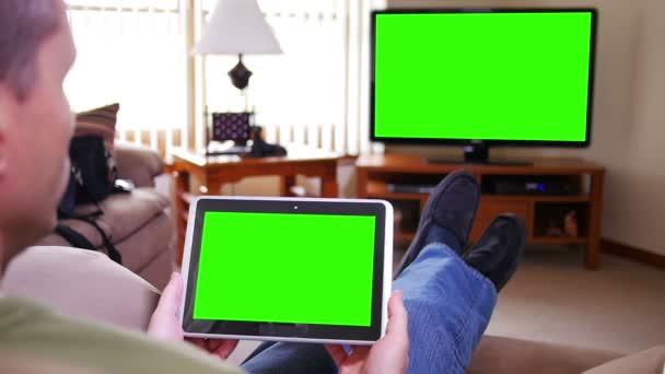 muž s ipad se dívá na televizi