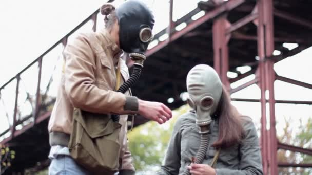 The guy with the girl in the gas masks smell the flower