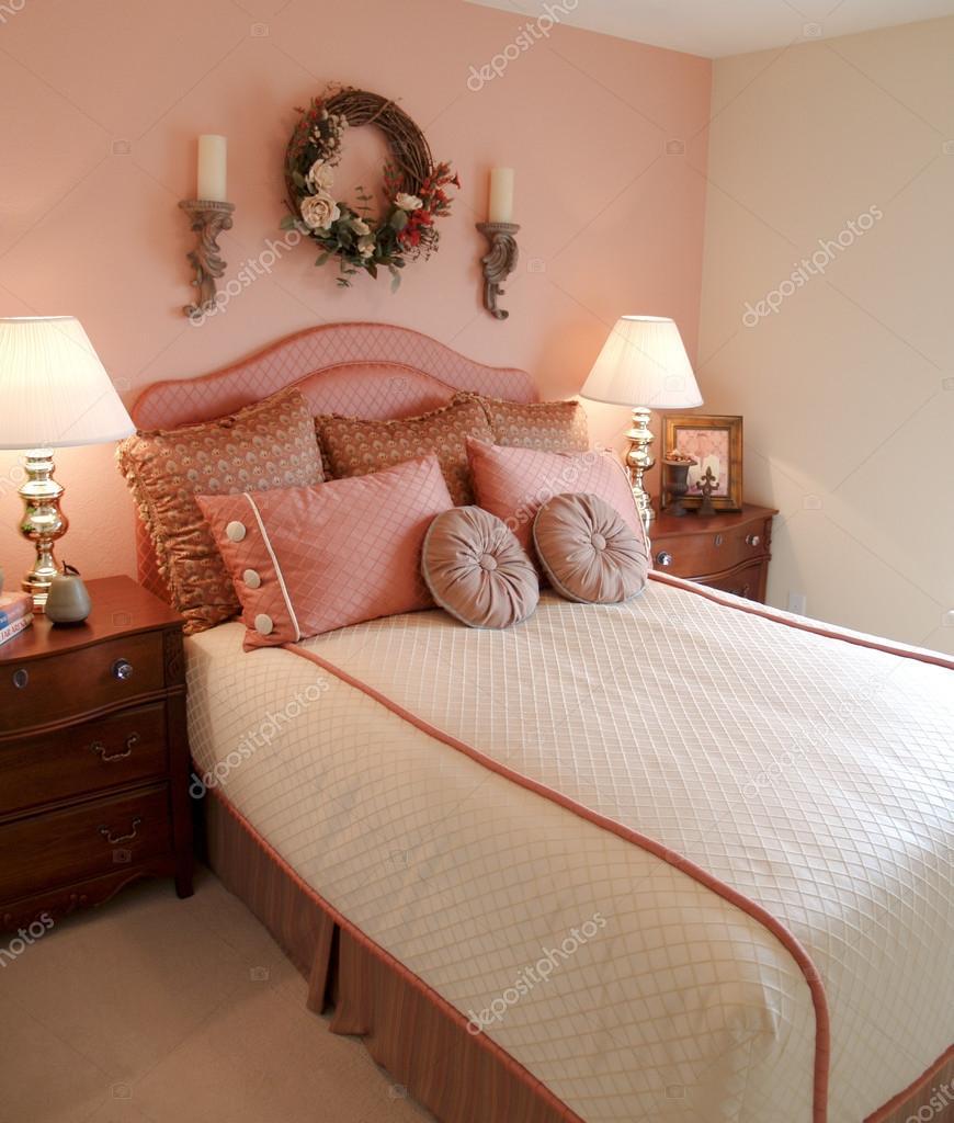 slaapkamer met roze accent muur focus op bed en beddengoed ...