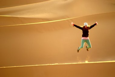 Woman leaping and dunes