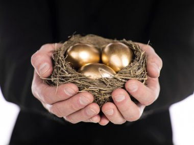 Businessman holding nest with gold eggs