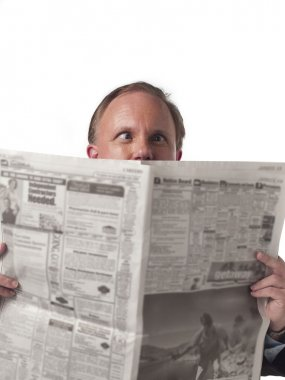 front view of a businessman holding newspaper with eyes cocked