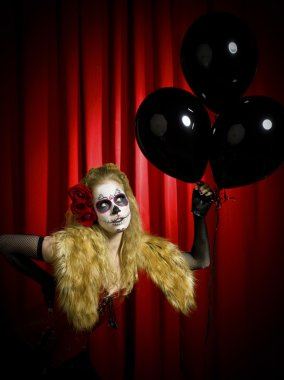 female wearing traditional sugar skull posing with balloons