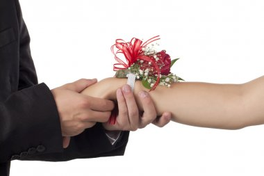 male hand holding a female hand with corsage