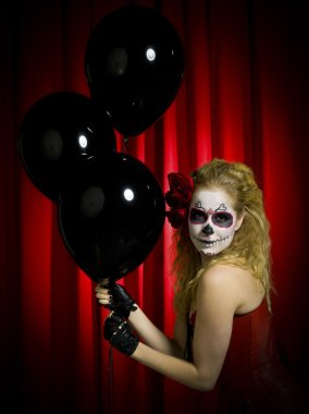 Portrait of a female holding black balloons