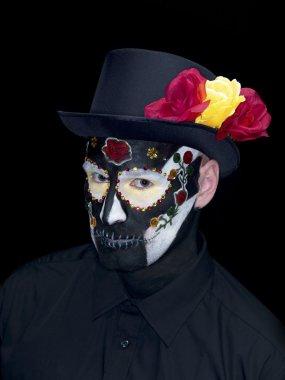 Portrait shot of a man in sugar skull make up over dark backgrou