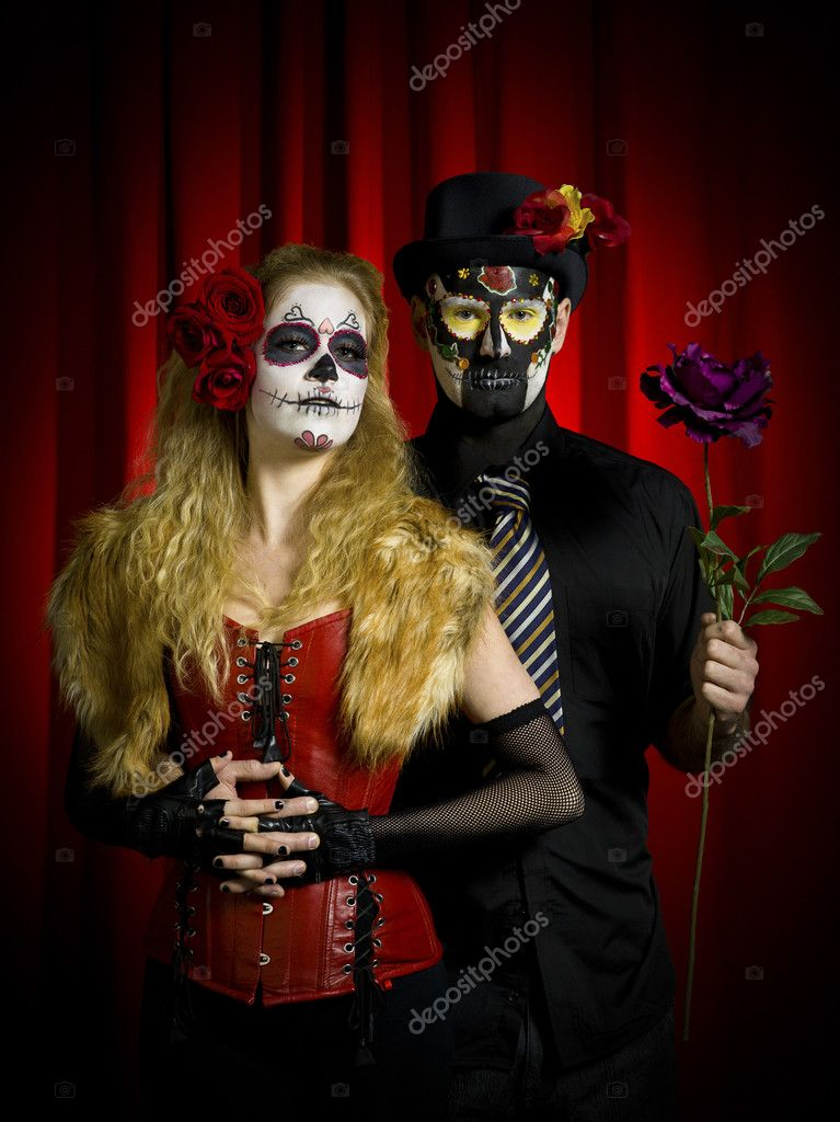 Portrait of a scary couple posing over red background