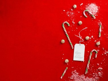 Close up shot of a broken candy canes with happy holidays tag