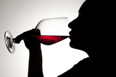 silhouette of a woman drinking red wine