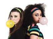 Photo young women standing back to back and blowing bubble gum