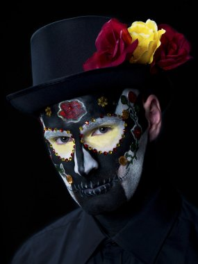 portrait shot of a scary man wearing face make up and hat