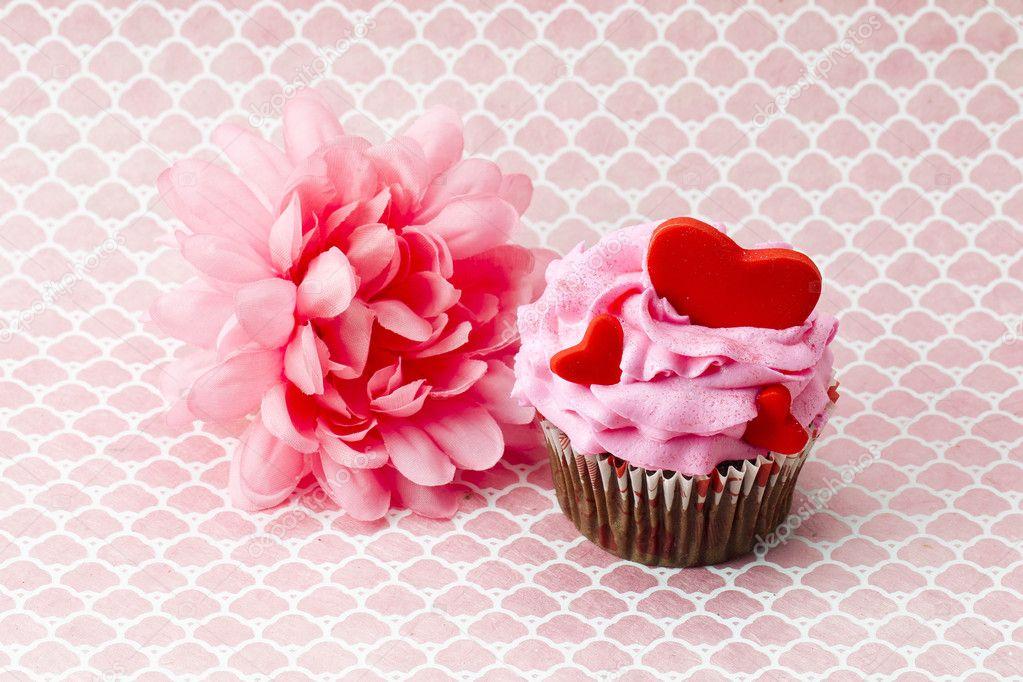 Eine Rosa Blume Neben Rosa Kuchen Mit Herzen Drin Stockfoto