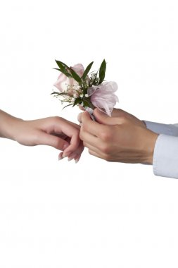 a guy putting a rose corsage on the womans wrist
