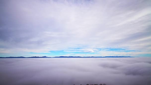 Clouds, dense layer of fog and mountain peaks