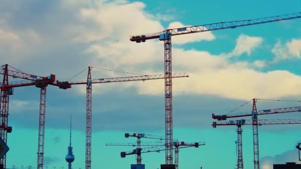 Arbeitskräne und wolkenverhangener Himmel im Berliner Baugebiet