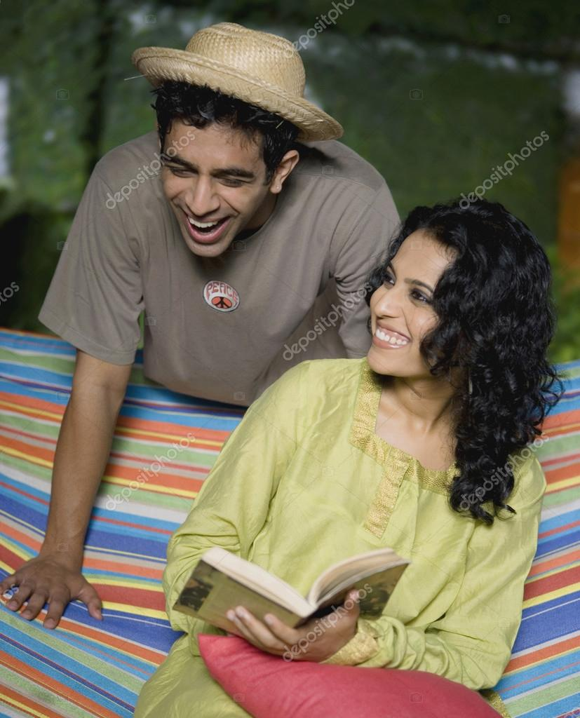 Couple reading book in hammock