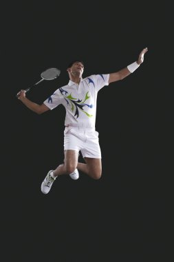badminton player with racket jumping
