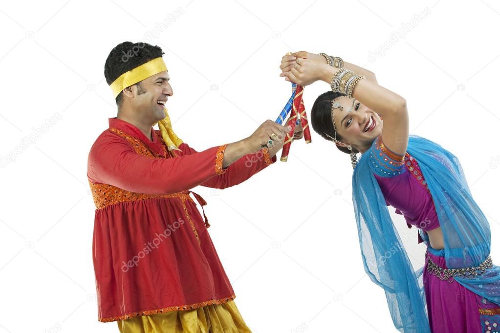 Gujarati couple performing dandiya dance isolated on white background