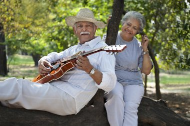 Old man plays on guitar for woman