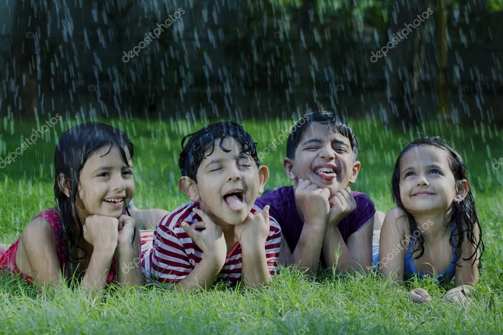 Happy boys and girls catching raindrops on tongue