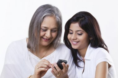 Grandmother and granddaughter with phone