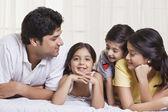 Fotografie usmívající se rodina ležet v posteli