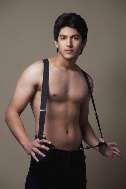Shirtless man wearing suspenders
