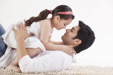 Little young girl sitting on father's stomach