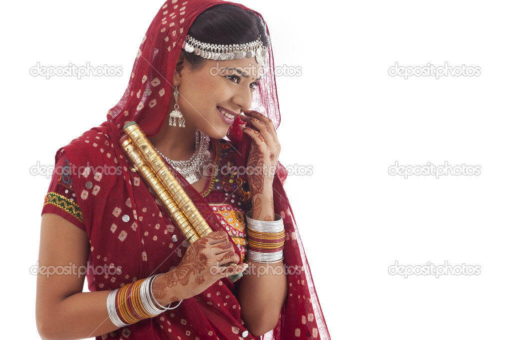 Portrait of a female dandiya dancer with sticks over white background