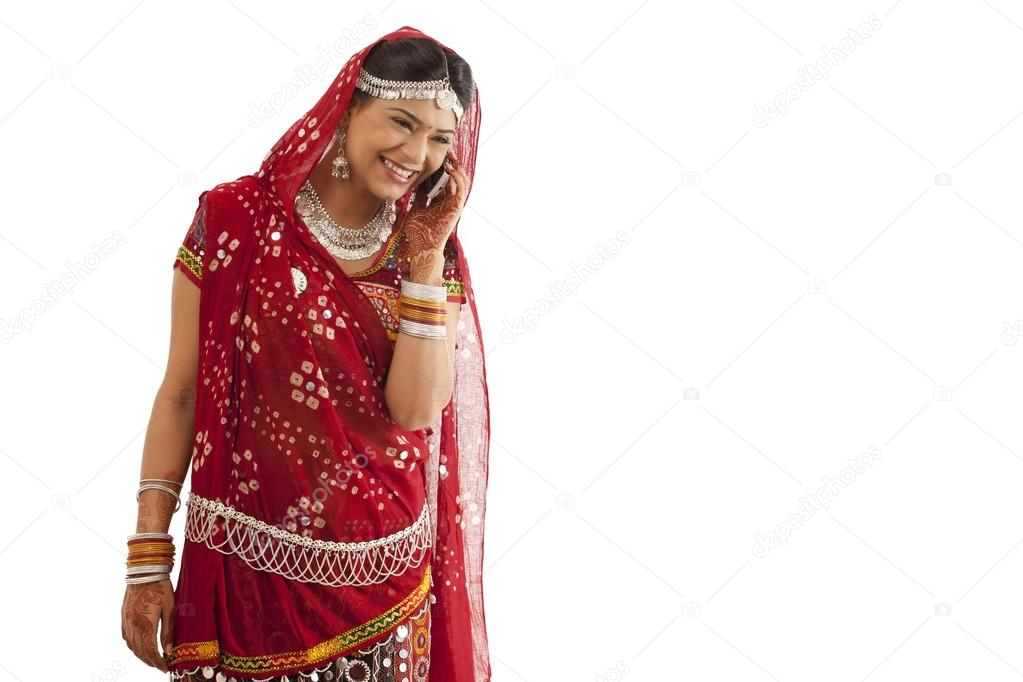 Female dandiya dancer talking on a mobile phone over white background