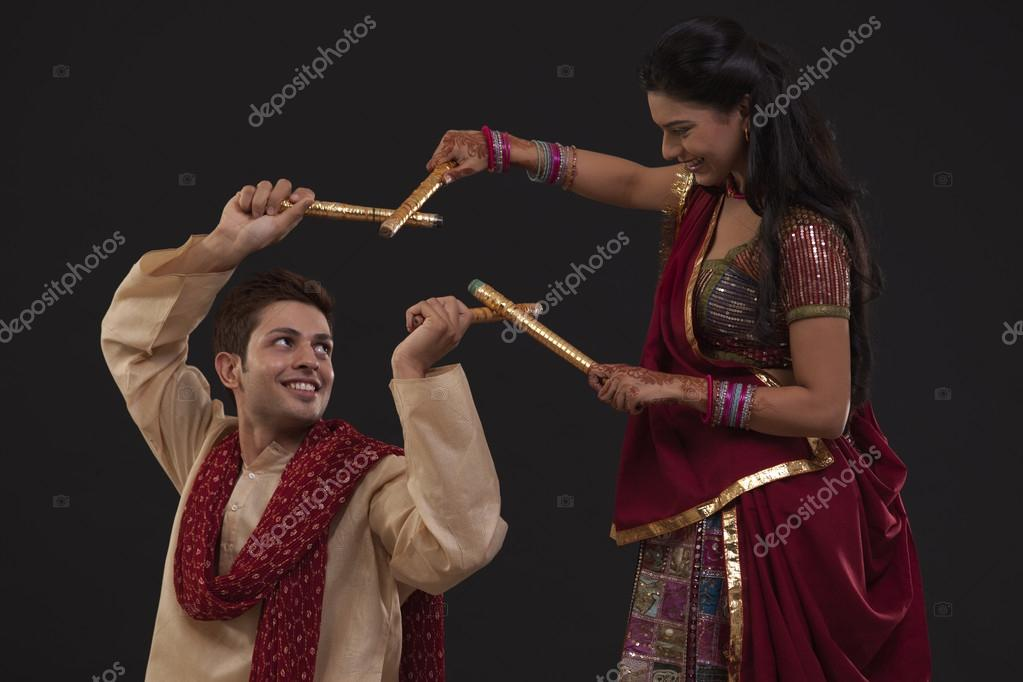 Portrait of couple dancing dandiya with sticks on black background