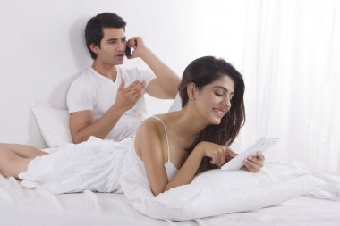 Young woman holding cell phone with man using digital