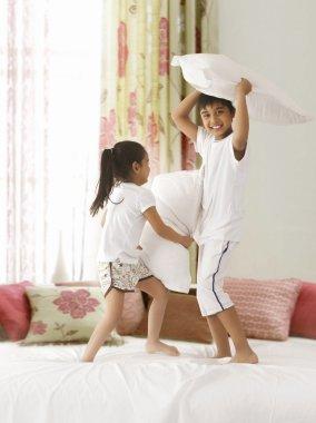 Siblings having pillow fight