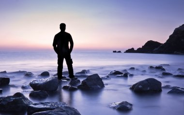 Man feeling freedom on beach during sunrise