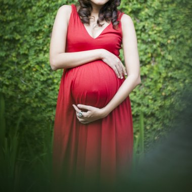 Image of pregnant woman touching her belly with hands relaxing o