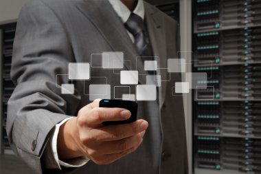 business man holds touch screen mobile phone in server room