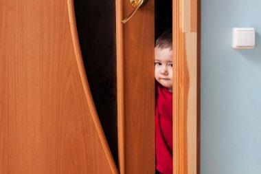 Child peeking from behind the door